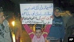 시리아 정부군의 폭격으로 아버지를 잃은 바바 아무르 지역 여자아이가 '시리아군의 폭격 중단'을 요구하는 내용의 플랜카드를 들고 있다.