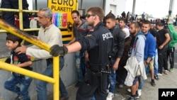 Para migran antri untuk mendapatkan makanan di kota Nickelsdorf, Austria dekat perbatasan Hungaria, Kamis (10/9).