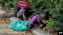 Dua orang demonstran di Bujumbura, Burundi berlindung dari tembakan polisi dalam aksi protes rusuh hari Senin (4/5).