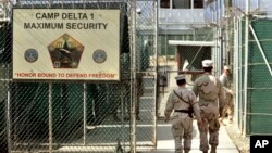 FILE - U.S. military guards enter the Camp Delta military-run prison, at the Guantanamo Bay U.S. Naval Base, Cuba, June 27, 2006.