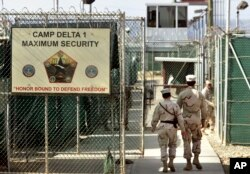 FILE - U.S. military guards enter the Camp Delta military-run prison, at the Guantanamo Bay U.S. Naval Base, Cuba, June 27, 2006.