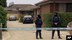 In this image made from video, police stand guard outside a raided property connected to a foiled terror attack, Nov. 20, 2018, in Melbourne, Australia.