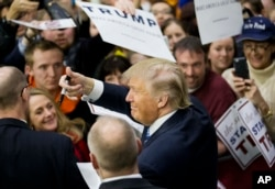 Republican presidential candidate Donald Trump gestures to the crowd as he signs autographs at a campaign event at Plymouth State University Sunday, Feb. 7, 2016, in Plymouth, N.H.