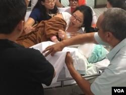Weni, yang datang dengan tempat tidur darurat, melihat untuk terakhir kalinya dan mengucapkan perpisahan kepada kedua putranya yang tewas dalam serangan bom bunuh diri di Gereja Santa Maria Tak Bercela, di Surabaya, Minggu, 13 Mei 2018. (Foto: VOA/Petrus Riski).