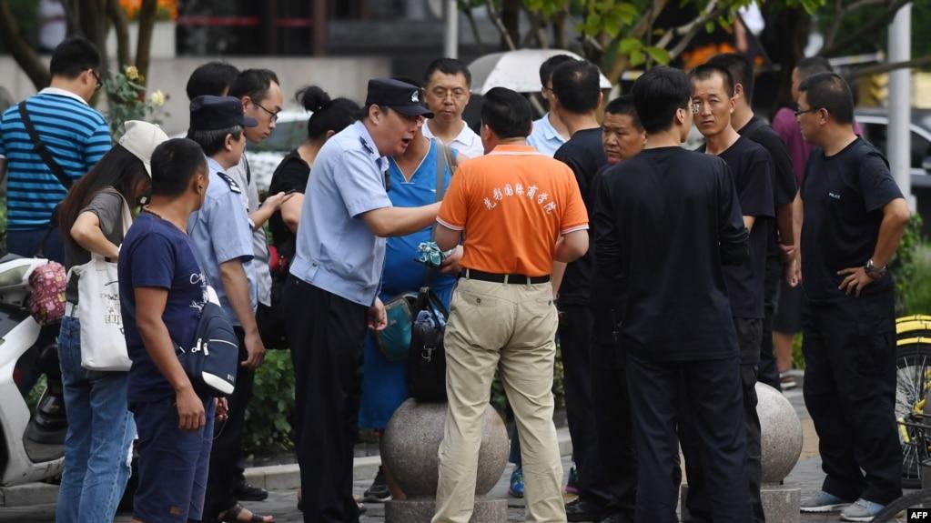 在北京的中国银监会附近,警察对中国网络理财民间集资受害者讲话,旁边是保安人员(2018年8月6日)。受害者从中国各地到北京请愿维权。