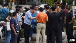 在北京的中國銀監會附近,警察對中國網絡理財民間集資受害者講話,旁邊是保安人員(2018年8月6日)。受害者從中國各地到北京請願維權。