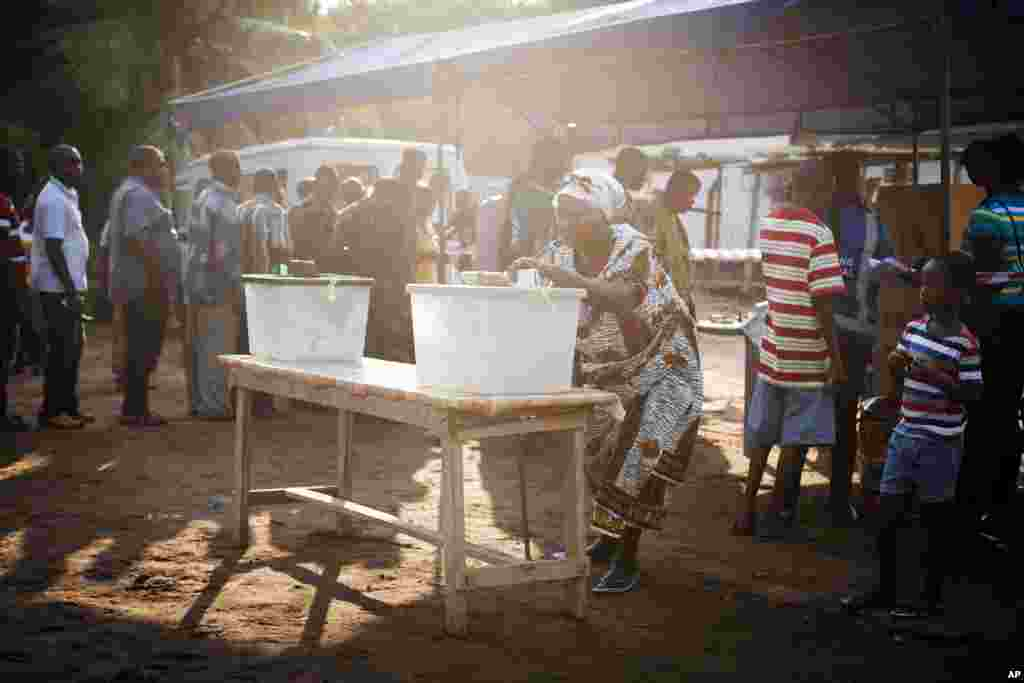 A woman casts her vote for the presidential election at a polling station in Accra, Ghana, December 7, 2012.