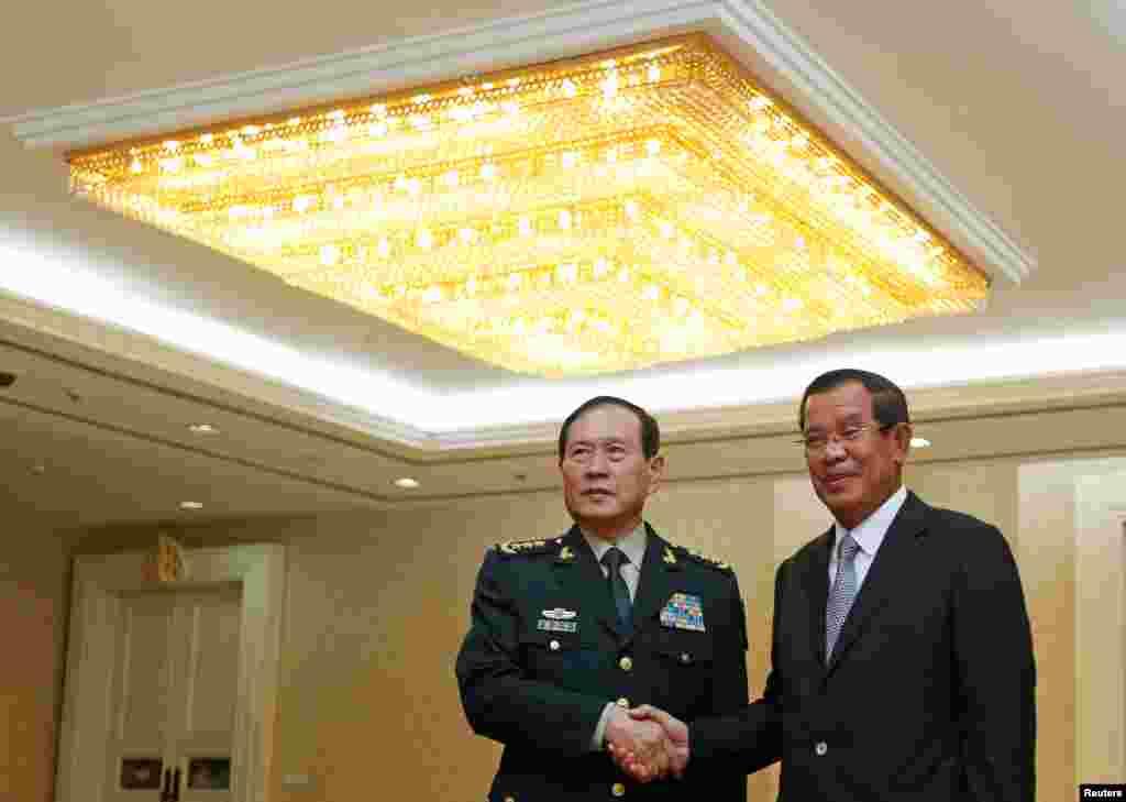 """2018年6月18日中国国防部长魏凤和(左)在柬埔寨金边会晤柬埔寨首相洪森。魏凤和6月16日抵达柬埔寨,出席在金边举办的中柬军事展览。路透社报道,柬埔寨国防部发言人索切特表示,中国承诺提供超过一亿美元的援助,柬埔寨可自行决定如何使用。这位发言人表示,与中国的合作为柬埔寨提供了数百辆军事运输车,柬埔寨指挥人员乘坐的汽车以及联合军演所需费用。另外,两国明年将再度举行""""金龙""""联合军演。"""