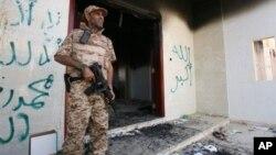 Một binh sĩ Libya đứng canh ở khu vực trước đây là Lãnh sự quán Mỹ đã bị đốt