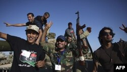 Chiến binh NTC ăn mừng sau khi chiếm được một chiếc xe bọc thép từ lực lượng thân Gadhafi ở thị trấn Wadi Dinar, ngày 21/9/2011