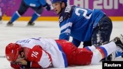 Atlet Hoki Es Rusia Alexei Yemelin menutupi wajahnya setelah terkena pukulan atlet FInlandia Lauri Korpikoski (kanan) dalam putaran kedua pertandingan perempat final hoki es pria di Olimpiade Musim Dingin 2014 di Sochi, Rusia (19/2).