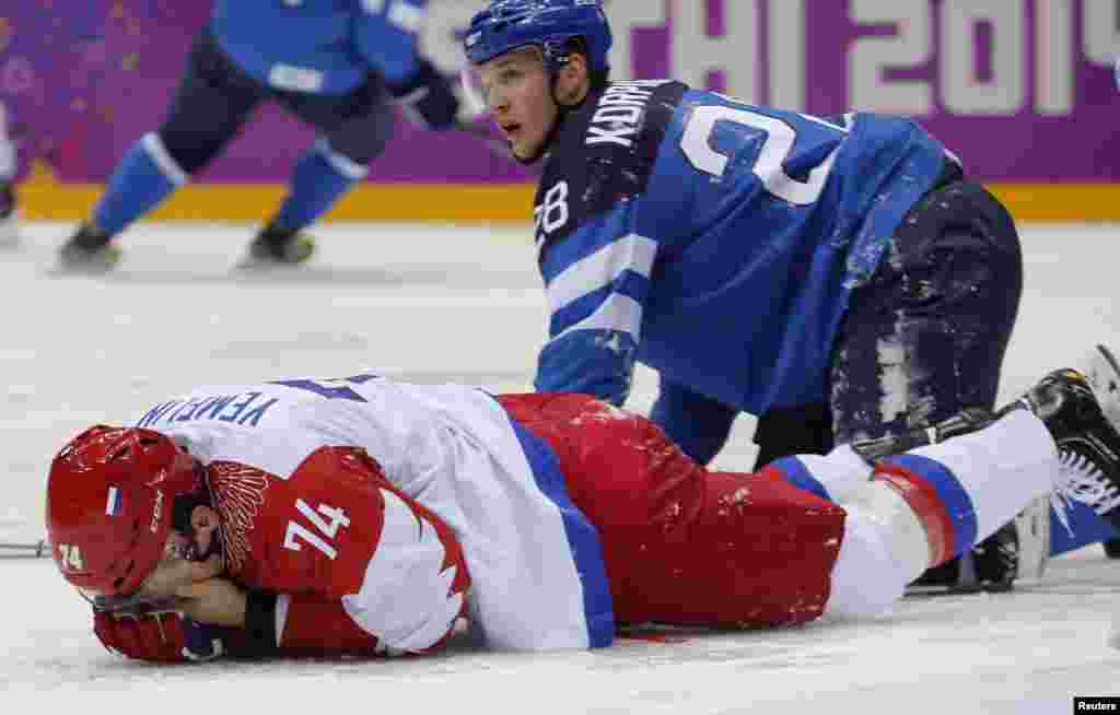 Russia's Alexei Yemelin holds his face after getting hit by Finland's Lauri Korpikoski (right) during the second period of the men's quarter-finals ice hockey game, Sochi, Feb. 19, 2014.