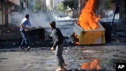 FILE - Turkish youths set fire to barricades in Diyarbakir, hours after violent protests by Kurds over the Islamic State group's advance on Kobani, Syria, Oct. 8, 2014.