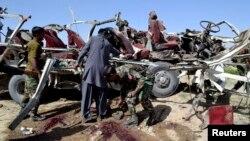 Petugas keamanan mengumpulkan bukti-bukti di dekat kendaraan yang hancur akibat ledakan bom di Quetta (23/5). Sedikitnya 11 personel keamanan dan dua warga sipil tewas dalam insiden tersebut.