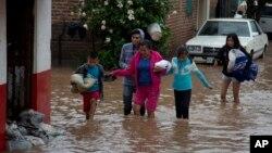 Các cư dân đi qua một con đường ngập nước ở Zoatlan, tiểu bang Nayarit ở Mexico, hôm 24/10.