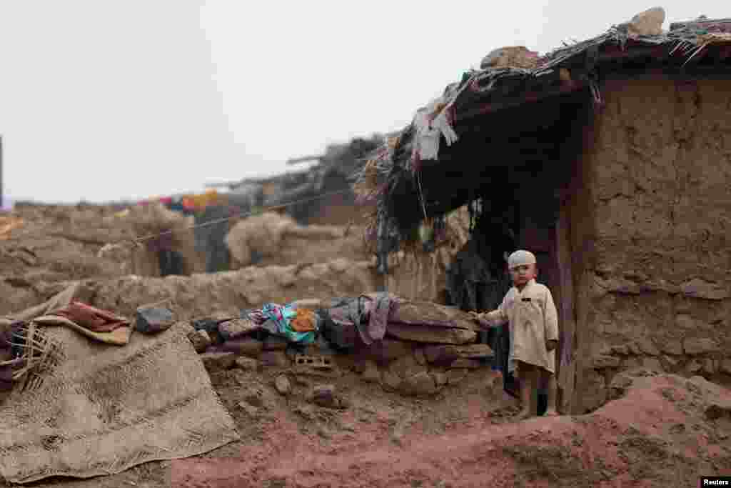 A boy stands beside his family home in an Afghan refugee camp in Islamabad, Pakistan.