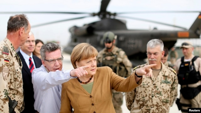 Germany's Chancellor Angela Merkel (C) points with German Minister of Defense Thomas de Maiziere as she makes a surprise visit to Bundeswehr base in Kunduz, Afghanistan, May 10, 2013.