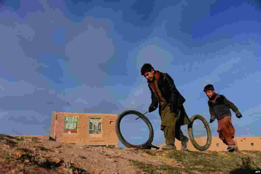 Dua anak Afghanistan bermain dengan ban bekas di pinggiran kota Herat.