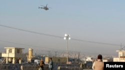 Afghan security forces keep watch as a NATO helicopter flies over a site in Jalalabad, (File photo).