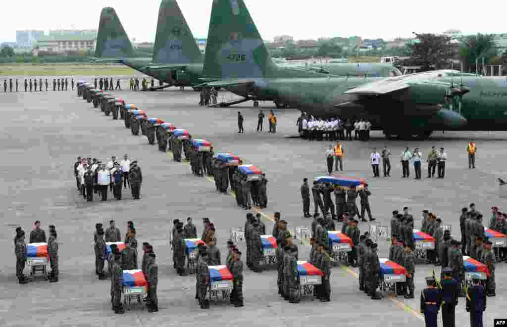 Philippine police commandos carry the flag-draped coffins of their fallen comrades from C-130 planes shortly after arriving at a military base in Manila as the country mourned dozens of policemen killed in a botched anti-terror operation.