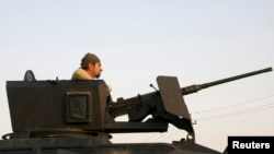 A member of the Kurdish Peshmerga forces stands in a military vehicle in Jalawla, Diyala province, Iraq, July 3, 2014.
