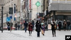 Only a few people, wearing mandatory medical masks, walk on the main shopping street in Essen, Germany, during the lockdown due to the COVID-19 pandemic on Tuesday, Feb. 2, 2021. (AP Photo/Martin Meissner)