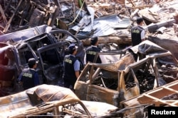 FILE - Indonesian forensic policemen walk past destroyed cars near the site of the Oct. 12, 2002, bomb blasts at Kuta on Indonesia's resort island of Bali, Oct. 18, 2002.