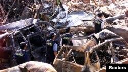 Polisi forensik berjalan melewati mobil-mobil yang hancur di dekat lokasi ledakan bom 12 Oktober 2002 di Kuta, Bali, 18 Oktober 2002. Tiga tersangka yang diduga terlibat pemboman di Indonesia antara tahun 2002-2003 akan diadili pengadilan militer AS. (Foto: Reuters)
