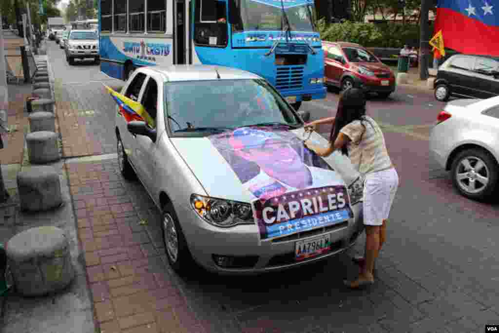 Esta joven decora su automóvil con un afiche con el rostro de Henrique Capriles [VOA].
