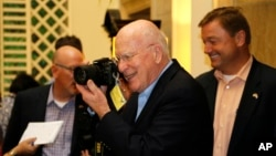 Sen. Patrick Leahy, D-Vt. turns his camera on reporters after a news conference in Havana, Cuba, June 27, 2015.