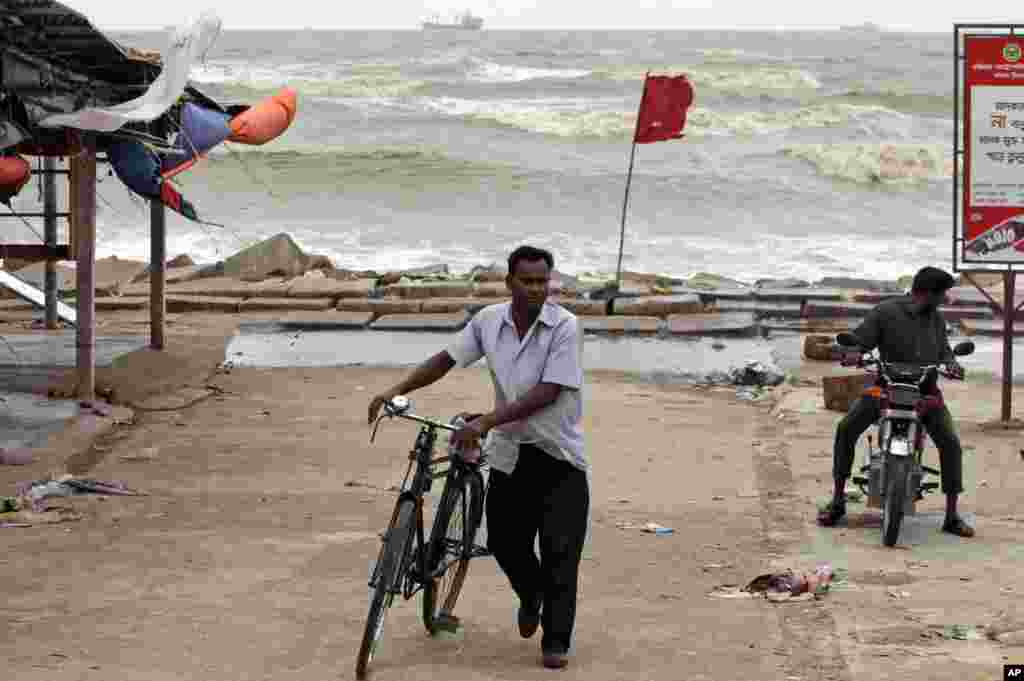 Bangladeshi commuters move past a red flag warning people of the coming tropical cyclone Mahasen by the coast of the Bay of Bengal in Chittagong, Bangladesh, May 16, 2013.