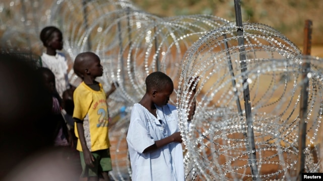 Internally displaced boys stand next to barbed wire inside a United Nations Missions in Sudan (UNMIS) compound in Juba December 19, 2013.