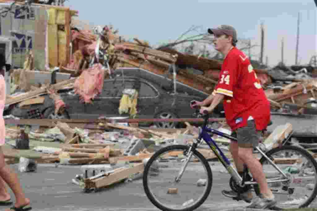 Los espectadores se abren paso entre los escombros dejados por el fuerte tornado en Tuscaloosa, Alabama.