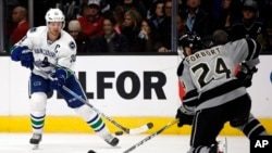 FILE - Vancouver Canucks center Henrik Sedin, left, of Sweden, passes the puck against Los Angeles Kings defenseman Derek Forbort during the first period of an NHL hockey game in Los Angeles, March 4, 2017. The NHL will play its first games in China this fall when the Kings and Canucks meet in Beijing and Shanghai.