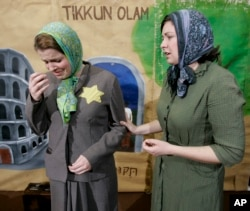 "FILE - Megan Stewart-Felt, right, playing the part of Irena Sendler, tries to persuade Jaime Walker, playing a Jewish mother, to give up her children during a rehearsal of ""Life in a Jar"" in Fort Scott, Kansas, Nov. 30, 2007."