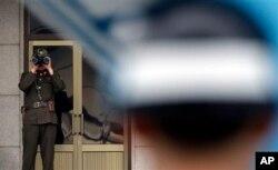 Binh sĩ Bắc Triều Tiên (trái) dùng ống nhòm nhìn sang phía miền Nam tại làng biên giới Bàn Môn Điếm.