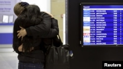 A couple embraces next to a flight information board at Pulkovo airport in St. Petersburg, Oct. 31, 2015.