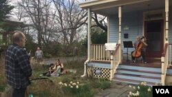 """Musician Jodi Beder plays her cello as neighbors enjoy the music on March 20, 2020, in Mount Rainier, Maryland. Beder plans to hold daily cello concerts from her front porch as the new coronavirus has led to """"social distancing measures."""" (Ashley Thompson/VOA)"""