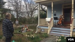 "Musician Jodi Beder plays her cello as neighbors enjoy the music on March 20, 2020, in Mount Rainier, Maryland. Beder plans to hold daily cello concerts from her front porch as the new coronavirus has led to ""social distancing measures."""