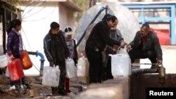 Orang-orang mengantri untuk mengisi wadah-wadah yang dibawanya dengan air di kawasan al-Rabwah yang berada di bawah kendali pemerintah (10/1), sebuah daerah pinggiran di Damaskus, Suriah. (foto: REUTERS/Omar Sanadiki)