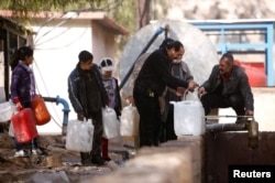 FILE - People queue as they fill containers with water in the government controlled al-Rabwah area, a suburb of Damascus, Jan. 10, 2017.