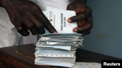 A man searches for his voting card at a polling station in Cameroon's capital, Yaounde (file photo).