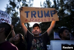 FILE - People protest outside the Luxe Hotel, where Republican presidential candidate Donald Trump was expected to speak in Brentwood, Los Angeles, California, July 10, 2015.
