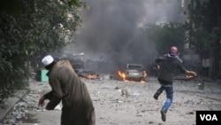 Dua orang demonstran melemparkan batu ke arah polisi di Kairo (21/11). Sedikitnya 22 tewas dalam bentrokan antara polisi dan demonstran di Mesir dalam 3 hari terakhir.