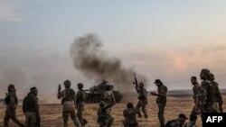 Tentara Turki dan pejuang Suriah yang didukung Turki berkumpul di pinggiran utara kota Manbij di Suriah dekat perbatasan Turki ketika Turki dan sekutunya melanjutkan serangan mereka terhadap kota-kota perbatasan yang dikuasai suku Kurdi di Suriah timur laut. (Foto: AFP/Zein A)