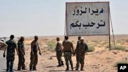 """Солдаты сирийской правительственной армии и проправительственных сил стоят у указателя """"Добро пожаловать в Дейр-аз-Зур"""" на входе в одноименный город в Сирии. 3 сентября 2017 г."""