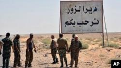"Foto yang dirilis 3 September 2017 oleh kantor berita resmi Suriah SANA, menunjukkan pasukan Suriah dan pria bersenjata pro-pemerintah yang berdiri di samping sebuah plakat dalam bahasa Arab yang berbunyi, ""Deir Ezzor menyambut Anda,"" di kota timur Deir Ezzor, Syria."