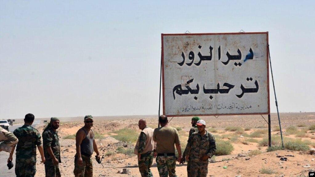 この写真は、シリアの公式報道機関であるサナ(SANA)が2017年9月3日に発表したもので、東アジアの都市ディール・エル・デ・エルの「Deir el-Zourがあなたを歓迎する」というアラビア語のプラカードの隣に立っており、 Zour、シリア。
