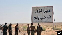 """This photo released Sept 3, 2017 by the Syrian official news agency SANA, shows Syrian troops and pro-government gunmen standing next to a placard in Arabic which reads, """"Deir el-Zour welcomes you,"""" in the eastern city of Deir el-Zour, Syria."""