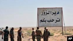 """叙利亚部队士兵和亲政府武装人员站在""""代尔祖尔欢迎你""""的路牌下 (2017年9月3日)"""